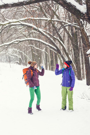 Girls giving high five to each other. Friends go through the winter forest. Women with backpacks stroll through the snow park.