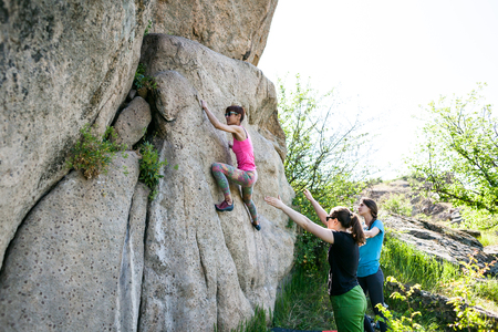 A rock climber climbs a rock and his partner insures. Athletes are bouldering outdoors. Group of friends involved in sports in the fresh air. Girl resting on the nature.