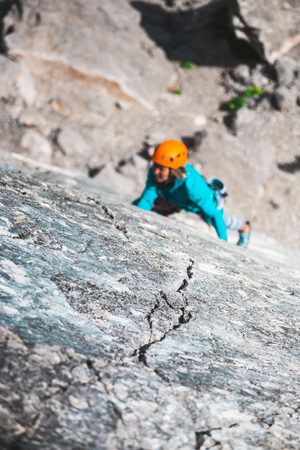 Climber on a rock. A woman overcomes a difficult climbing route. A crack on the rock. The relief of the stone against the background of a climbing girl.