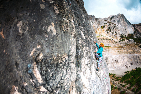 The girl climbs the rock. The climber in helmet trains on a natural relief. Extreme sport. Active recreation in nature. A woman overcomes a difficult climbing route. Stock Photo