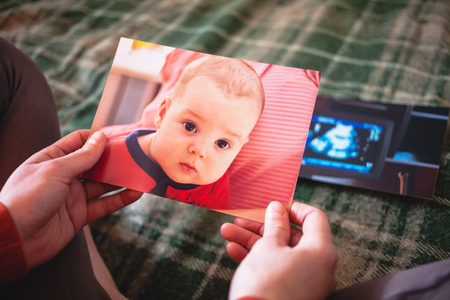 Photos of a small child. A woman looks at old photographs and remembers the events of the past. Nostalgic memories. Newborn baby on paper photos.