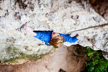 An emotional boy climbs the rock. The child is engaged in rock climbing on a natural relief. The sports kid actively spends time. Exercise in the fresh air. Rock climbing on difficulty.