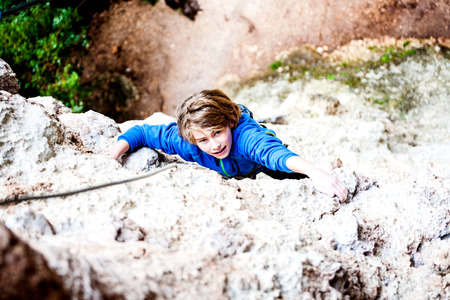 The boy climbs the rock. The child is engaged in rock climbing on a natural relief. The sports kid actively spends time. Exercise in the fresh air. Stock Photo