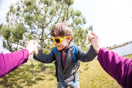 A boy in sunglasses plays with his parent. The kid fools around with Mom. A child is having fun outdoors. Fisheye lens. Smiling toddler. Stock Photo