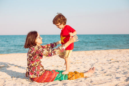 Mother plays with her baby on the beach. A woman with her son on the seashore. A boy and his mother are sitting on the sand.