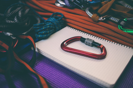 Notepad, rope and carbine. Equipment for rock climbing. Notebook and equipment for safety and travel.