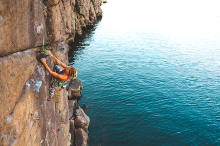 the girl climber climbs the rock above the water. outdoor activities. extreme sport
