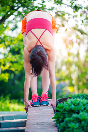 A woman is doing stretching in a city park. Morning training in nature. Yoga practice. Fitness. The girl warms up before jogging.