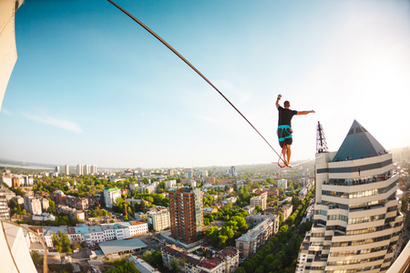 A man walks along a line stretched between two buildings. Extreme entertainment. Fear of heights. The man is balancing over the city.