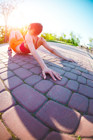 Yoga in the streets of the city. A girl is doing exercises at dawn. A woman is training in the park. Brunette meditates in nature. Quiet place for training in a bustling city. Stock Photo