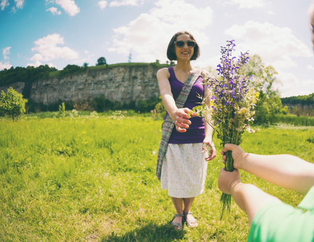 The boy gives his mother a bouquet of wild flowers. A woman is walking with her son in a meadow. A gift for mother's day. The girl takes a bunch of flowers. The child congratulates mom.
