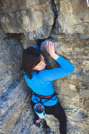 The girl climbs the rock. A woman overcomes a difficult climbing route. A rock climber on a rock. Doing sports outdoors. Stock Photo