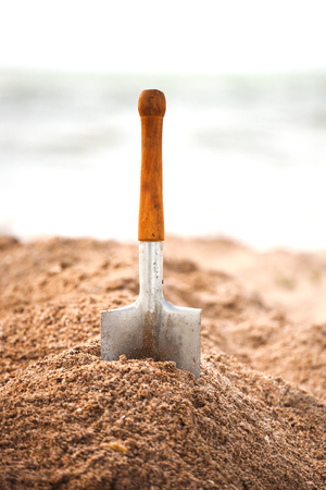 A metal spade in the sand. Children's shovel on the seashore. Working tool against the background of the sea coast. Stok Fotoğraf