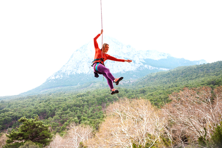 A woman is hanging on a rope in the background of beautiful mountains. The climber goes down. The girl goes down after overcoming a difficult climbing route.