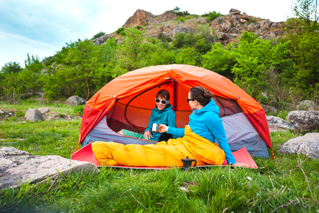 Two girls are sitting in a tent. Stock Photo