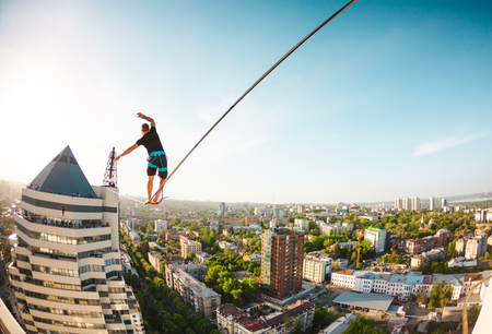 A man walks along a line stretched between two buildings. A man catches balance at altitude. Highline over the city.