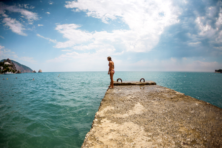 A slender girl in a swimsuit is standing on the pier. A woman is standing on a dock against the background of the sea. The blonde is preparing to jump into the water. Rest on the sea.
