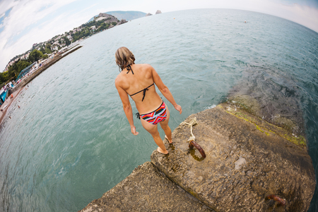 A slender girl in a swimsuit is standing on a breakwater. A woman is on a dock. The blonde jumps into the water. Rest on the sea. An athlete is practicing to dive off the pier. Fisheye lens