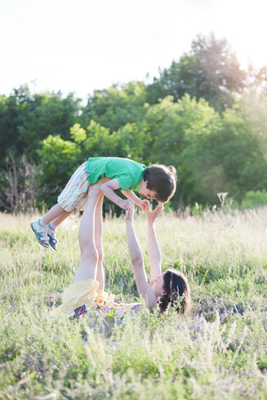 Mom plays with his son in active games. Gymnastics with a child in the field. The boy is lying on mother's legs. The woman raises the baby on her feet. A pair yoga on the grass. Akroyoga.