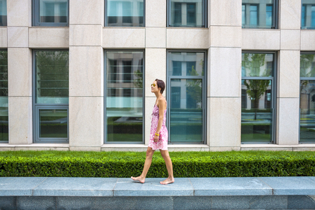 A barefoot woman walks along a stone border. The brunette is walking along the street. A slender girl in a summer dress against the backdrop of a city building.