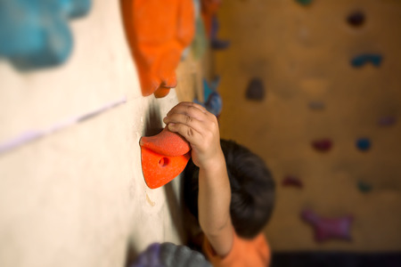 The climber trains on the climbing wall. The boy is trained to climb on an artificial relief. The child goes in for sports. Active lifestyle. Stock fotó