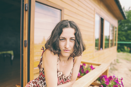 Portrait of a thoughtful woman. Girl with beautiful eyes. Emotions of calm and reverie. Brunette on the background of a wooden house. A woman is resting on the veranda at home. Wrinkles near the eyes. Archivio Fotografico