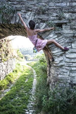 The girl climbs the stone wall. A woman in a summer dress climbs the wall of an old destroyed building. Brick fence. The climber is hanging on the city building. Strengthening the ruined castle.