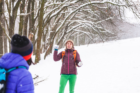 Friends play snowballs. Women are walking in the winter forest. Girls are praying in winter games. Merry vacation in a snow park. Stok Fotoğraf