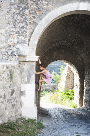 A woman in a dress is climbing a brick wall. The girl climbs on a stone fence. Climber on a city street. The wall of the old destroyed building.