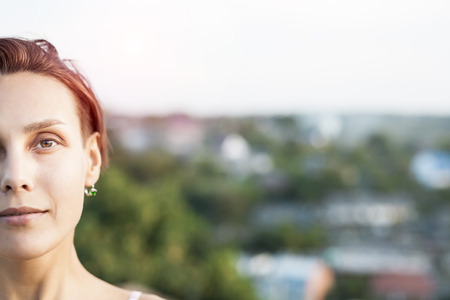 Portrait of a young woman. Half face. Girl on the background of the city. Brunette with short hair.