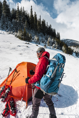 Camping in the snow. Winter trekking in the mountains. Orange tent, snowshoes and trekking poles. A man with a backpack sets a tent on the snow. Extreme journey. Equipment for winter hiking.