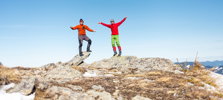 Two mountaineers climbed to the top of the mountain. Men are balancing on the rocks against the sky. Friends in the mountain hiking. The climbers raised their hands up.