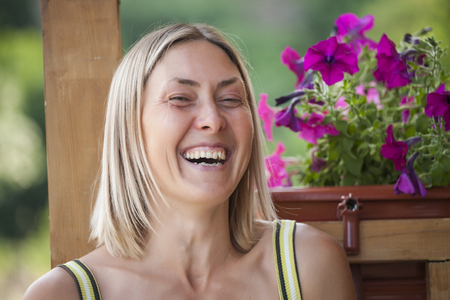 Portrait of a smiling woman. Blonde on the background of a wooden house. A woman is resting on the veranda at home. Stok Fotoğraf