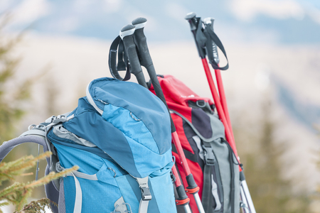 Two backpacks in the background of snow-capped mountains and blue sky. A backpack on the snow. Active lifestyle. Trekking in winter. Equipment for hiking. Trekking sticks.
