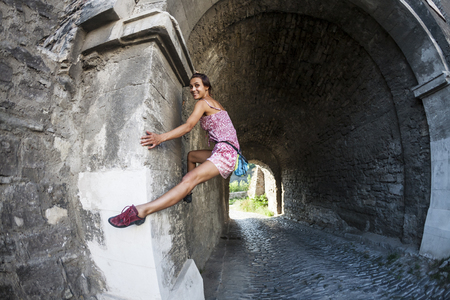 A woman in a dress is climbing a brick wall. The girl climbs on a stone fence. Climber on a city street. The wall of the old destroyed building. Fisheye lens.