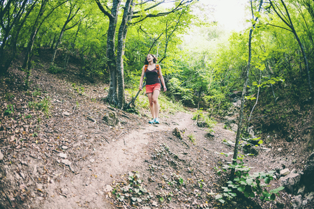 The girl is walking through the forest. A young woman with a backpack travels through picturesque places. A tourist walks along a mountain path. Fisheye lens.