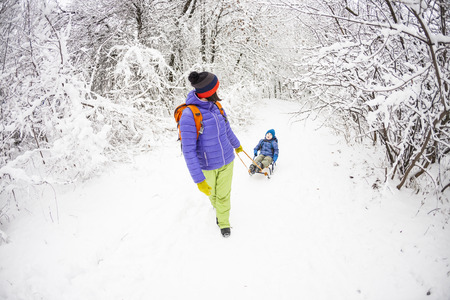 A woman is carrying a child on a sled. Mom walks with her son over the snow-covered forest. Cheerful winter vacation. Winter fun. Baby on the sleigh.