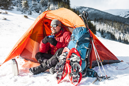 A man drinks from a mug near the tent in the winter. Tent, backpack, tracking sticks and snowshoes on the background of the mountains. Camping in the snow. Active rest and mountain climbing in winter.