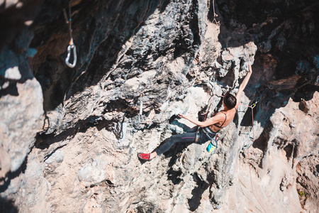 A woman climbs the rock. Climbing in nature. Fitness outdoors. Active lifestyle. Extreme sports. The athlete trains on a natural relief. Rock climbing in Turkey. Standard-Bild