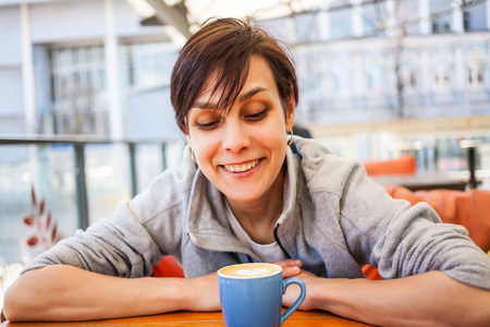 Morning refreshing drink in a blue cup. Smiling girl drinks coffee in a coffee shop. A young woman is sitting at a table in a cafe. Portrait of a beautiful brunette. Stock Photo