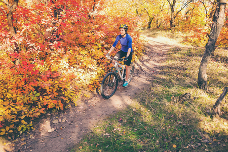 The girl with a backpack rides a bike in the autumn park. Slender woman trains in nature. Sports in the forest. Tourist rides on a dirt trail. Traveling by bike.