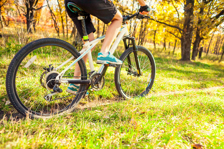 Biking in the forest. Girl rides a bike on a forest trail. Woman riding her bike in the park. Bicycle touring. Travel to scenic places. Autumn trees. Stock Photo