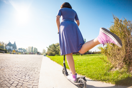 Slender girl in a dress and sneakers rides a scooter on the sidewalk. The woman put her foot to push away from the ground.