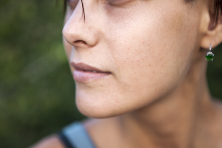 Skin aging. Female face close up. Problem skin of the face. Pigmented spots and freckles. Sunny suntan on the face of a young woman. Stock Photo