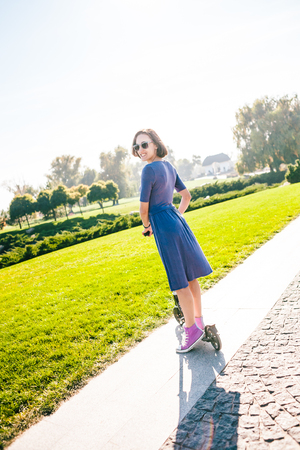 The girl rides a scooter in the park. Slim woman in dress have fun. Smiling brunette on a walk. Stock fotó