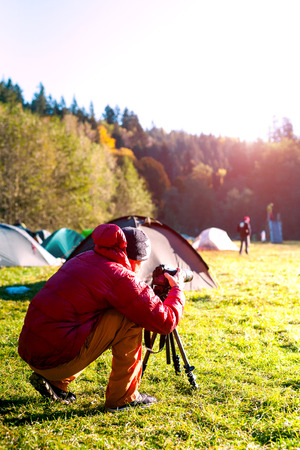 A photographer takes pictures of nature. Camera on a tripod. A man photographs beautiful views. Camping in the mountains.