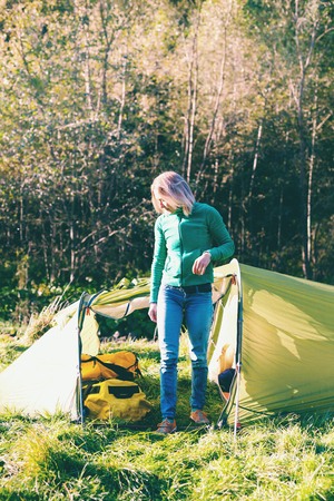 The girl near the tent. Camping in the forest. The woman left the tent. Travel with a backpack and tent. Morning awakening in nature.