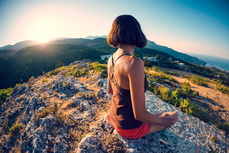 A girl is sitting on top of a mountain at sunset. A woman is engaged in yoga. Meditation is far from civilization. Contemplation of beautiful nature. View of the mountains. Beautiful sunset light.