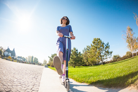 Woman riding a scooter. The girl in a dress rides a scooter in the park. Brunette pushes off the road. Feet in sneakers.