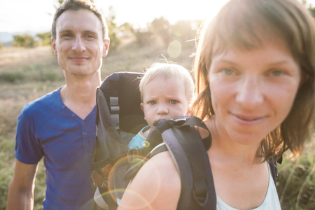 The family travels with the child. A woman carries her son in a backpack. The husband and wife took the child to the mountains. Traveling with children. A man is walking with his family.